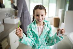 Smiling girl holding toothpaste and toothbrush in bathroom. Portrait of smiling girl holding toothpaste and toothbrush in bathroom Royalty Free Stock Photography