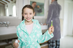 Smiling girl holding toothpaste and toothbrush in bathroom. Portrait of smiling girl holding toothpaste and toothbrush in bathroom Royalty Free Stock Image
