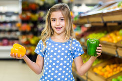 Smiling girl holding two pepper Stock Photos