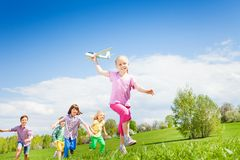 Smiling girl holds airplane toy with kids running Royalty Free Stock Photo