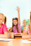 Smiling girl holds arm up behind her classmates Stock Photography