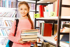 Smiling girl holds books near shelf in library Royalty Free Stock Photos