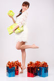 Smiling girl holds boxes with gifts and stands on one leg Stock Photos