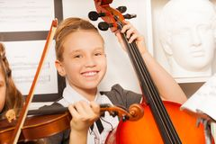 Smiling girl holds cello with other friend near Royalty Free Stock Image