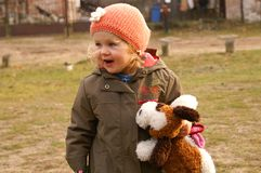 Smiling girl holds dog. Small girl holds plush dog in hat stock images