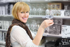 Smiling girl holds glass in shop Stock Photos