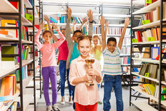 Smiling girl holds golden cup, kids jump behind. Smiling girl holds golden cup and other kids jumping behind in the library Royalty Free Stock Photo