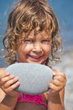 Smiling girl holds in hands pebble on seacoast Royalty Free Stock Photos