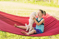 Smiling girl holds maltese dog on hammock Royalty Free Stock Images