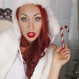 Smiling girl holds red christmas toy. Beautiful woman model in white fur, suprise Stock Photos