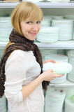 Smiling girl holds some plates in shop. Smiling girl wearing scarf holds some white plates in shop; shallow depth of field Royalty Free Stock Photography