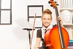 Smiling girl holds string to play violoncello Royalty Free Stock Images