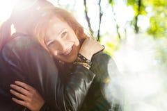 Smiling girl hugging best friend. Smiling girl hugging her best friend during autumn weather in the park Stock Photo