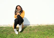 Smiling girl hugging a cat. Portrait of pretty Papuan girl with curly hair dressed in yellow t-shirt, black pants and white shoes - smiling young Indonesian Royalty Free Stock Photography