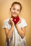 Smiling girl hugging red knitted heart Royalty Free Stock Photos