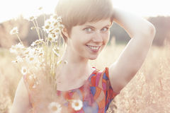 Smiling girl hugs armful of daisies Stock Photography