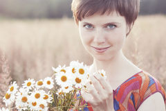 Smiling girl hugs armful of daisies Royalty Free Stock Images