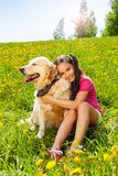 Smiling girl hugs cute dog sitting on the grass royalty free stock photography