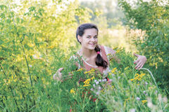 Smiling girl hugs tansy outdoors Stock Image
