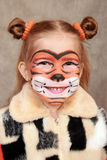 Smiling girl in the image of a tiger Stock Photography