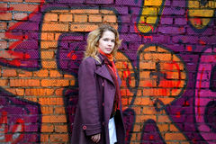 Smiling Girl In Front Of A Graffiti Wall Stock Image