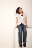 Smiling girl in jeans and white shirt sitting Royalty Free Stock Image
