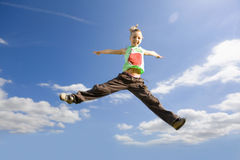 Smiling girl jumping with arms outstretched in sky Royalty Free Stock Images