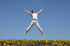Smiling girl jumping in field Stock Photo