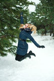 Smiling girl jumping in pinewood Stock Images