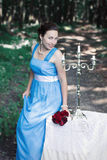 Smiling girl keeps bouquet of red roses and sits down on a table. Smiling girl in a blue dress keeps bouquet of red roses and sits down on a table with a white Royalty Free Stock Photography