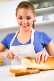 Smiling girl in kitchen cutting bread Royalty Free Stock Photos