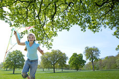 Smiling girl with kite running in field Stock Image