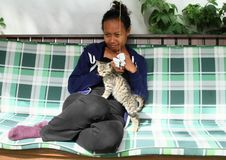 Smiling girl with a kitten. Smiling Papuan girl in blue jaket, black pants and purple socks - young woman petting grey tabby cat on green swing Royalty Free Stock Image