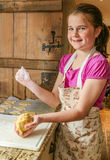 Smiling girl kneading biscuit (cookie) mixture. Young girl smiling kneading dough whilst baking in an apron stock photos
