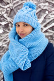 Smiling girl in a knitted blue scarf, and cap stands Stock Photos