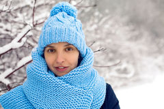 Smiling girl in a knitted blue scarf, and cap stands Royalty Free Stock Photos