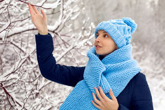 Smiling girl in a knitted blue scarf, and cap stands Royalty Free Stock Photography