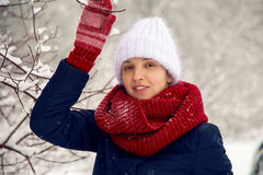 Smiling girl in a knitted red scarf, white hat and mittens Stock Image