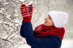 Smiling girl in a knitted red scarf, white hat and mittens Royalty Free Stock Photography