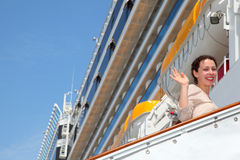 Smiling girl on ladder goes to the big cruise ship Stock Image