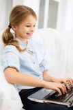 Smiling girl with laptop computer at home Stock Images