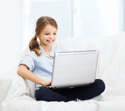 Smiling girl with laptop computer at home Stock Photos