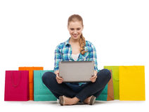 Smiling girl with laptop comuter and shopping bags Royalty Free Stock Image