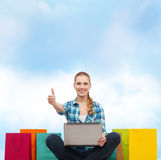 Smiling girl with laptop comuter and shopping bags. Shopping, gesture, technology and internet concept - smiling girl with laptop computer and shopping bags over royalty free stock image