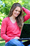 Smiling girl laptop in park Royalty Free Stock Images