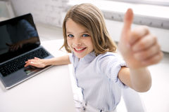 Smiling girl with laptop showing thumbs up at home Stock Image