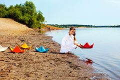 Smiling girl launches paper boat in lake Royalty Free Stock Photos