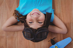 Smiling girl laying on the floor wearing aviator glasses and hat. With toy airplane next to her Royalty Free Stock Images