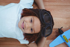 Smiling girl laying on the floor wearing aviator glasses and hat. With toy airplane next to her Royalty Free Stock Image