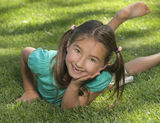 Smiling Girl Laying on Grass Stock Image